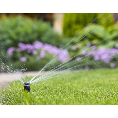 A sprinkler watering a lawn of green grass